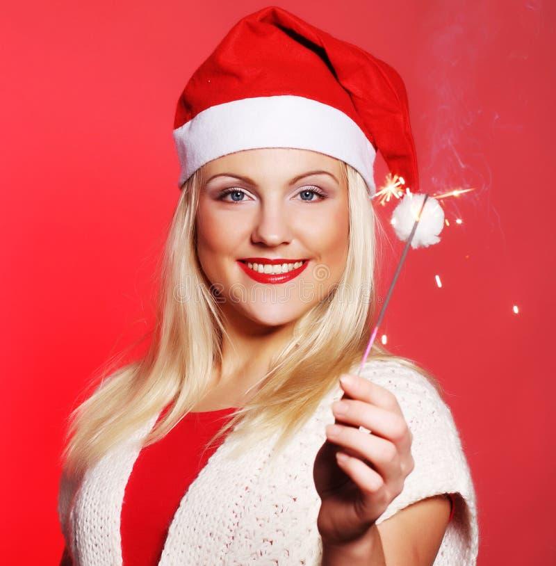 Girl in Santa hat holding sparklers stock photo