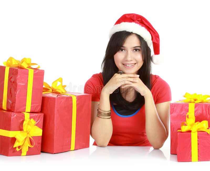 Girl in santa hat with pile of xmas gifts royalty free stock image