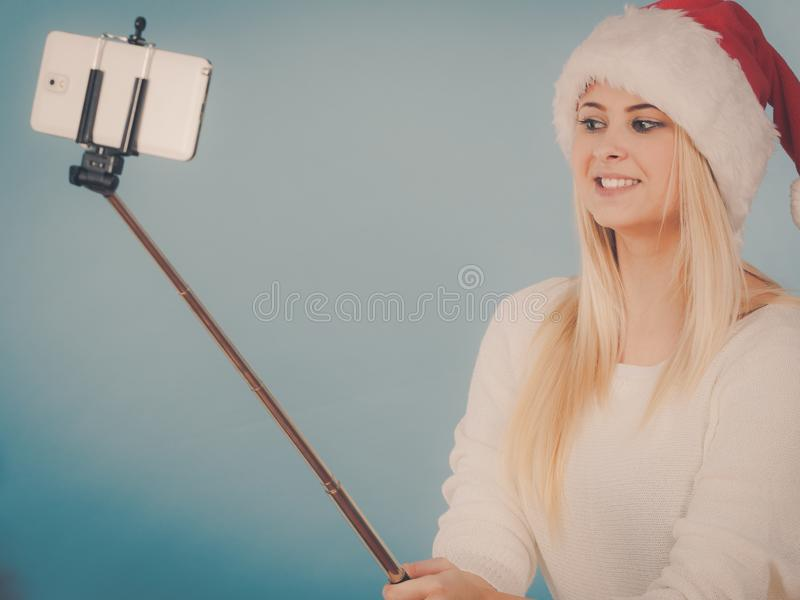 Girl in santa hat taking picture of herself using selfie stick stock photography