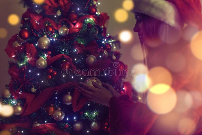 Girl in Santa hats placing a ornament on a Christmas tree royalty free stock photos