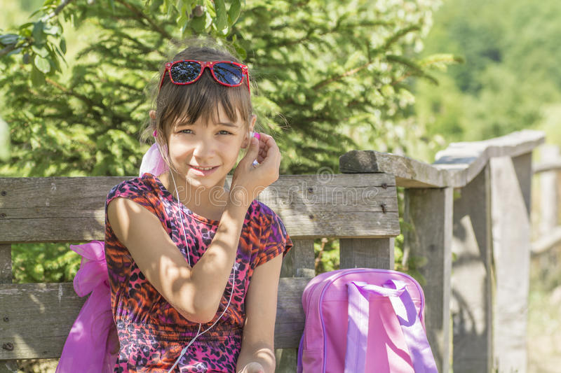 The girl sat down to rest listening to the player, with a backpack for travel royalty free stock photo