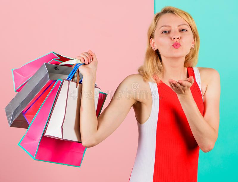 Girl satisfied with shopping. Tips to shop sales successfully. Girl enjoy shopping or just got birthday gifts. Woman red. Dress hold bunch shopping bags blue stock images