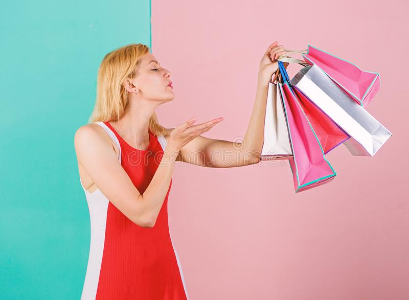 Girl satisfied with shopping. Tips to shop sales successfully. Woman red dress hold bunch shopping bags blue pink. Background. Girl enjoy shopping or just got stock photography