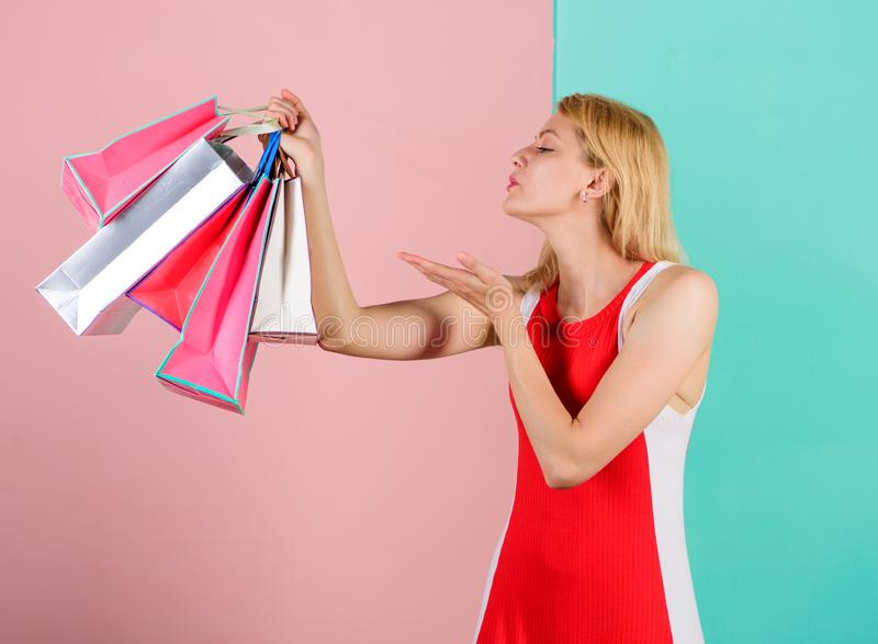 Girl satisfied with shopping. Tips to shop sales successfully. Woman red dress hold bunch shopping bags blue pink. Background. Girl enjoy shopping or just got royalty free stock photography