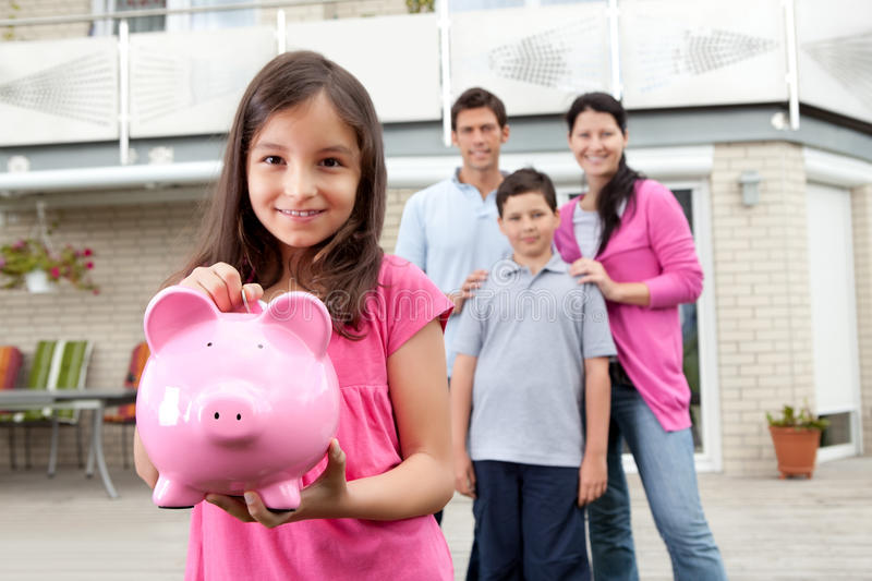 Girl saving money with family at the back. Beautiful little girl inserting coin in a piggy bank with her family in background stock photo
