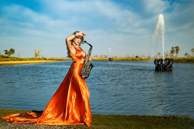 Girl with sax smiles, flirts. Happy blonde woman with big bust plays, performs on goldy saxophone in beautiful dress stock photography