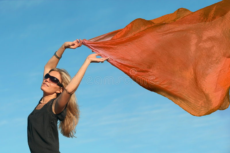 Girl with a scarf. Beautiful blond woman running with a orange scarf stock photos