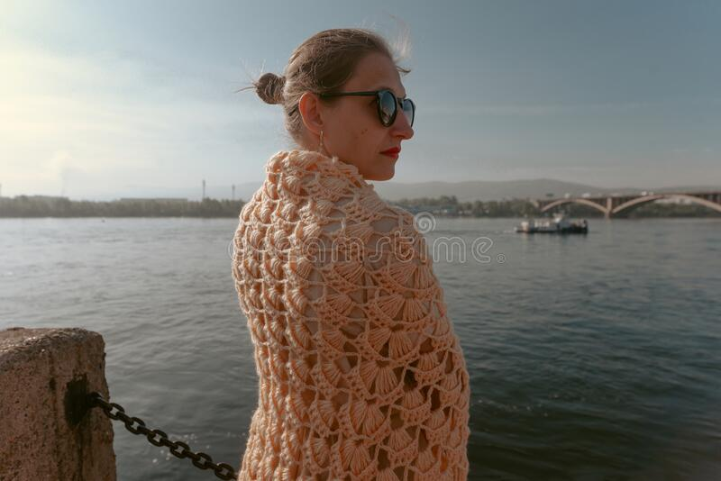 Girl in a scarf awaits her lover on the pier.  stock photo