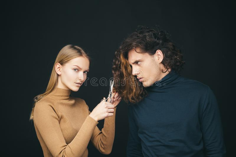 Girl scheming an evil plan of cutting off a curly hair in a man. A smart wily woman has wonderful schemes like a crook royalty free stock image