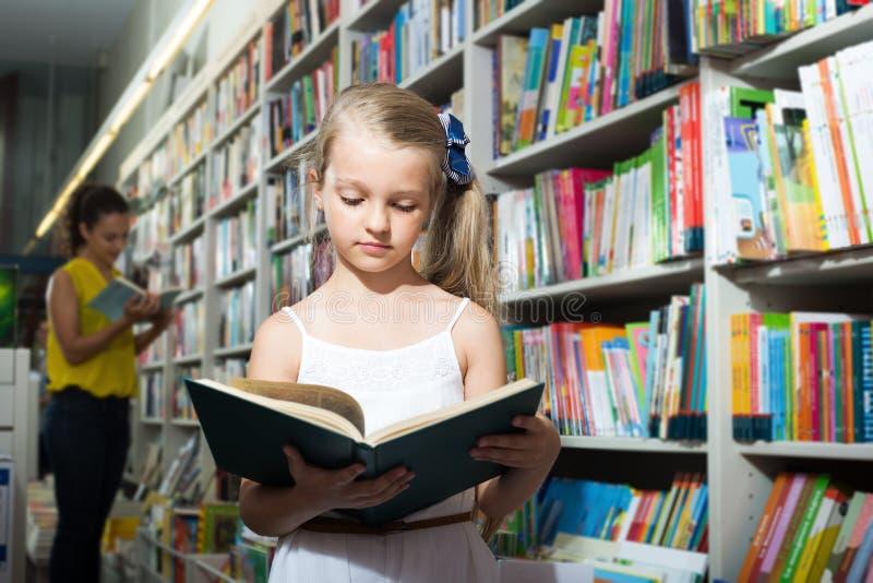 Girl in school age taking open chosen book. In shop royalty free stock image