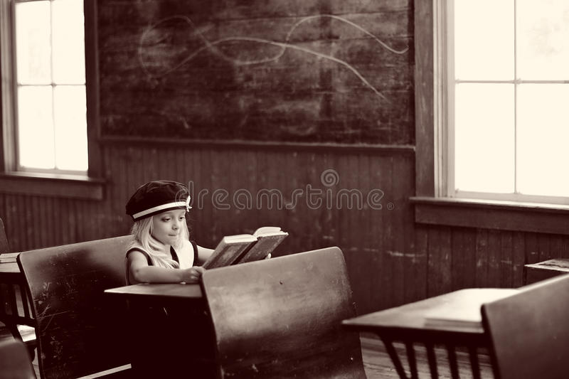 Girl at school desk. Young girl sitting and reading at an antique school desk in a classroom royalty free stock photo