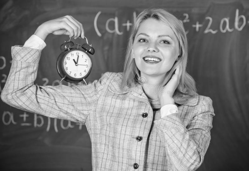 Girl school lecturer. Welcome teacher school year. Health and daily regime. Educator start lesson. She cares about. Discipline. Woman teacher hold alarm clock stock photo