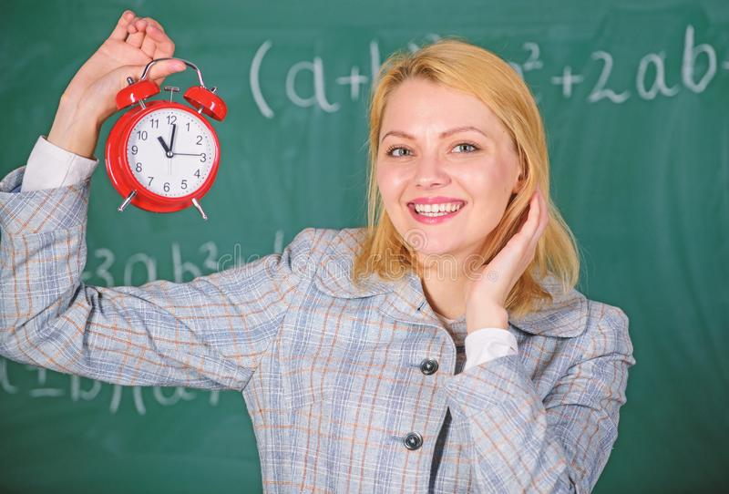Girl school lecturer. What time is it. Lessons schedule. Welcome teacher school year. Health and daily regime. Educator royalty free stock photo