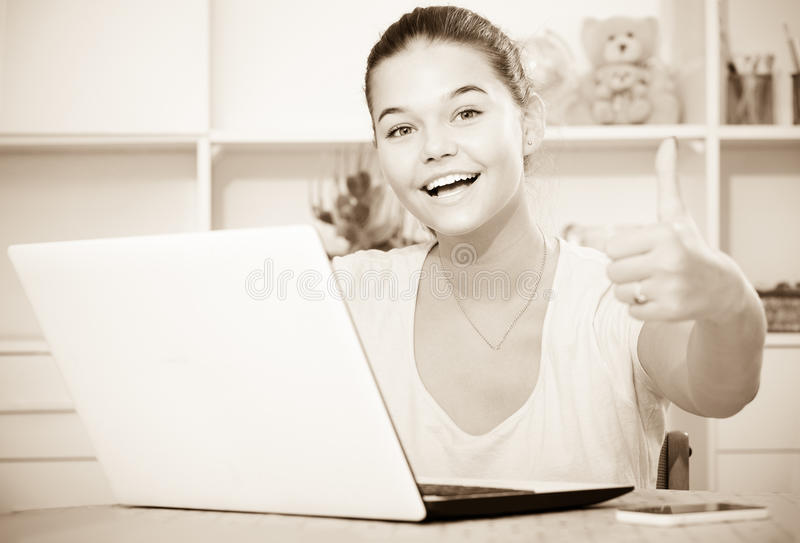 Girl school pupil sitting with laptop and showing thumbs up. Young smiling girl school pupil sitting with laptop and showing thumbs up royalty free stock photos