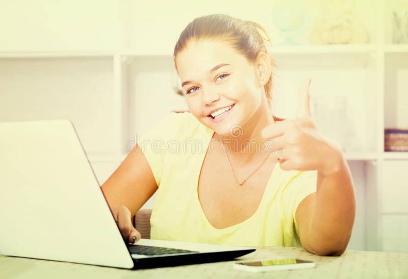 Girl school pupil sitting with laptop and showing thumbs up. Young smiling european girl school pupil sitting with laptop and showing thumbs up royalty free stock photography