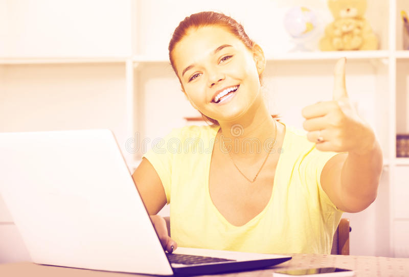 Girl school pupil sitting with laptop and showing thumbs up. Young smiling russian girl school pupil sitting with laptop and showing thumbs up royalty free stock photography