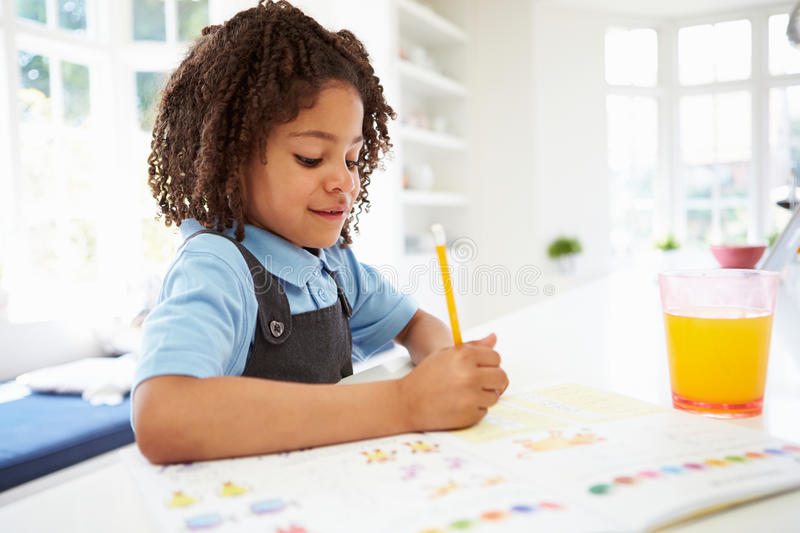 Girl In School Uniform Doing Homework In Kitchen. Using Pencil Writing In Textbook royalty free stock images