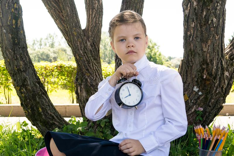 Girl in school uniform holding a watch in front of him, back to school royalty free stock image