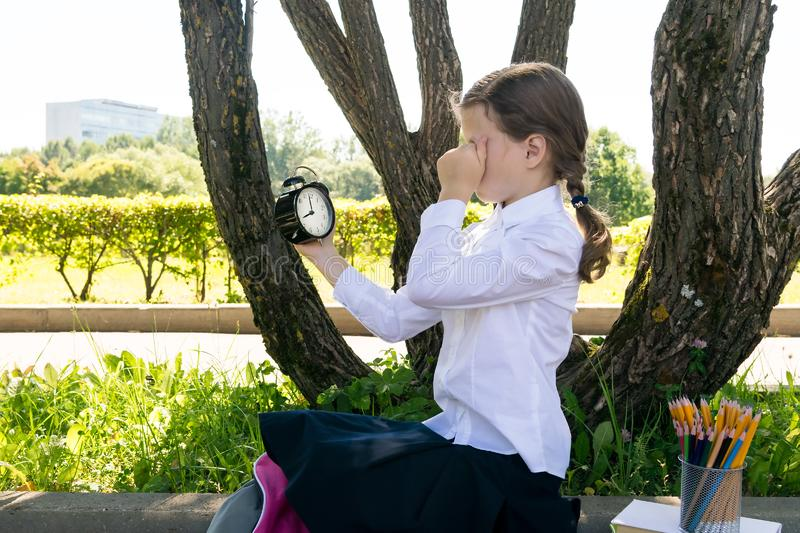 Girl in school uniform holding a watch in front of him, side view, back to school stock photos