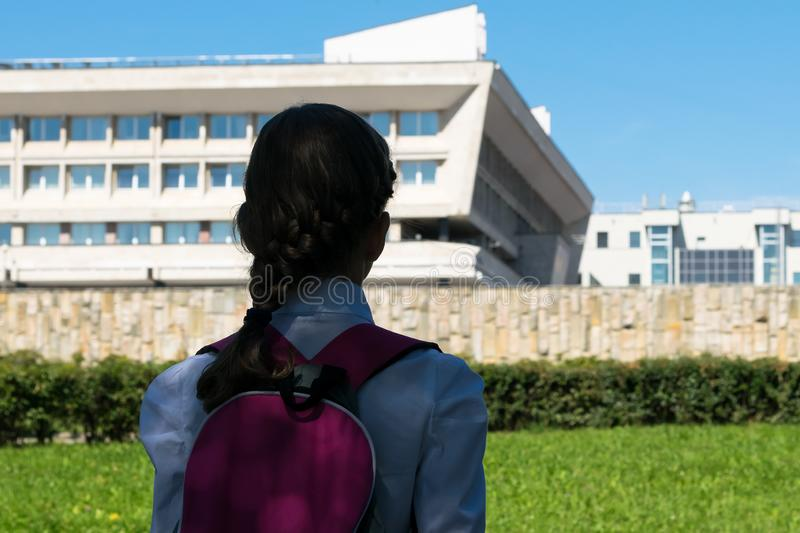 Girl in school uniform looking at the school building , rear view royalty free stock image
