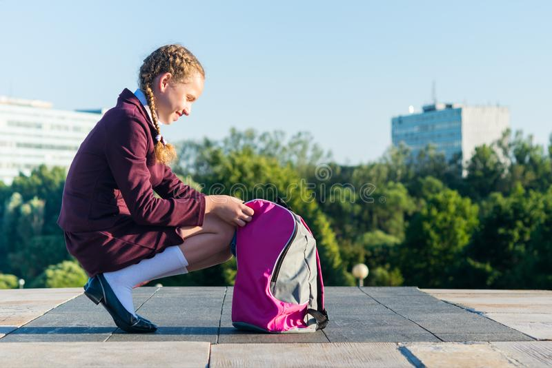 Girl in a school uniform opens a pink backpack for textbooks. Girl in a school uniform opens pink backpack for textbooks royalty free stock photos