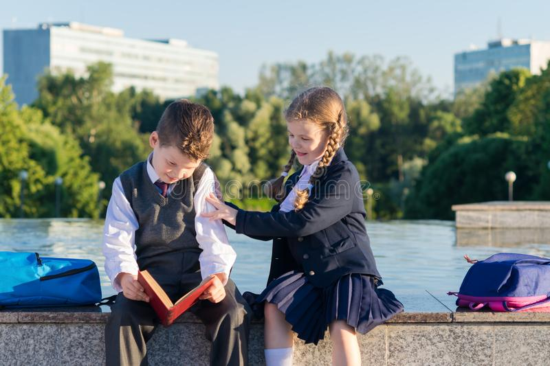 Girl in school uniform prevents a boy from reading a book royalty free stock photo