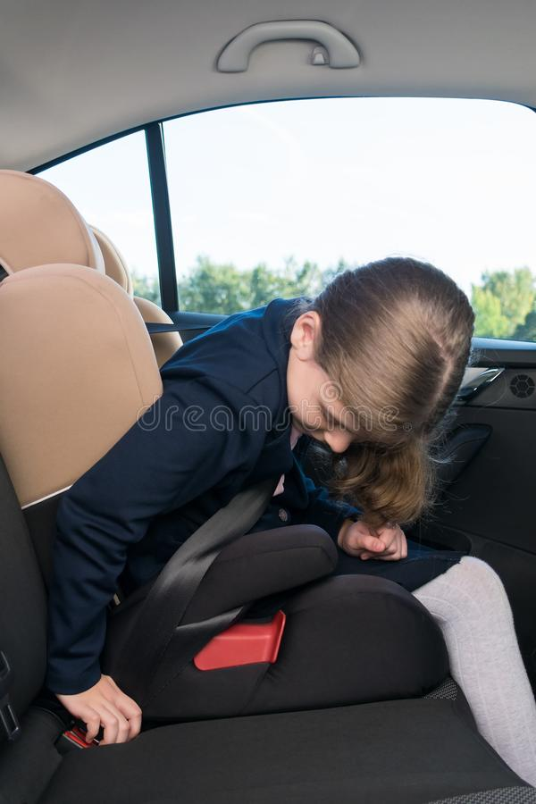 Girl in a school uniform sits in a child seat in a car and fastens his seat belt stock images