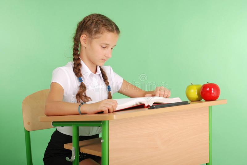 Girl in a school uniform sitting at a desk and reading a book. Isolated on green royalty free stock images