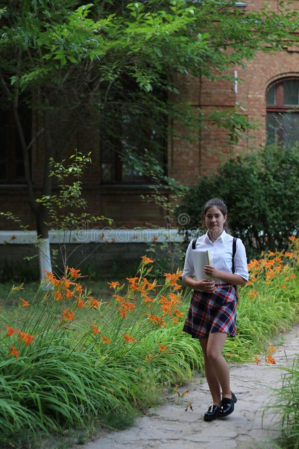 Girl schoolgirl with a folder in his hands royalty free stock images