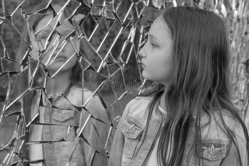 Girl schoolgirl looks sad in the broken mirror. Black and white photo stock image