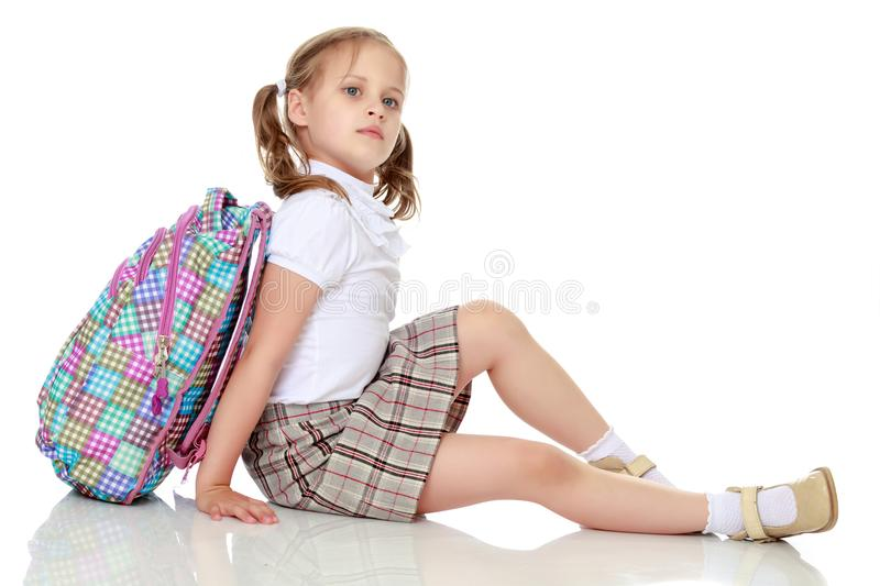 Girl schoolgirl sitting on the floor royalty free stock image