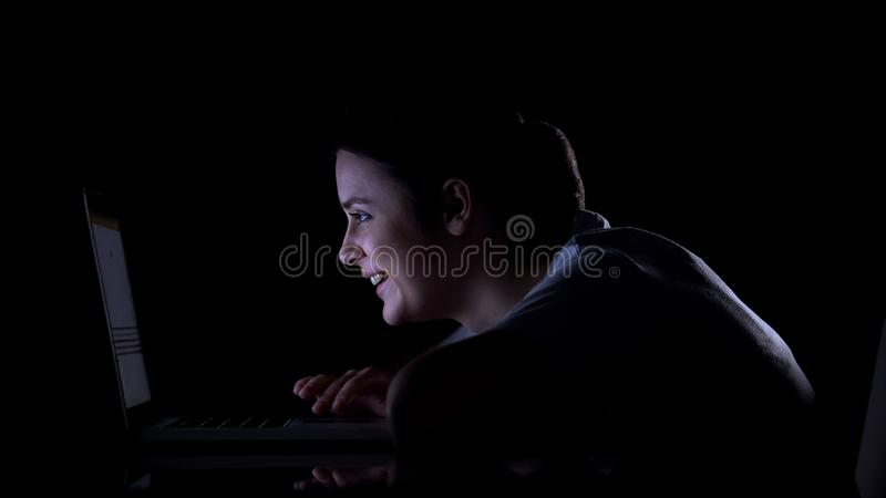 Girl scrolling social networks on laptop and smiling, reading posts and messages. Stock photo stock photography