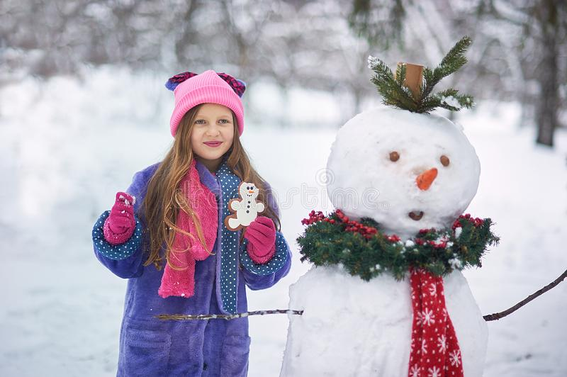 Girl sculpts a snowman in the Park. stock images