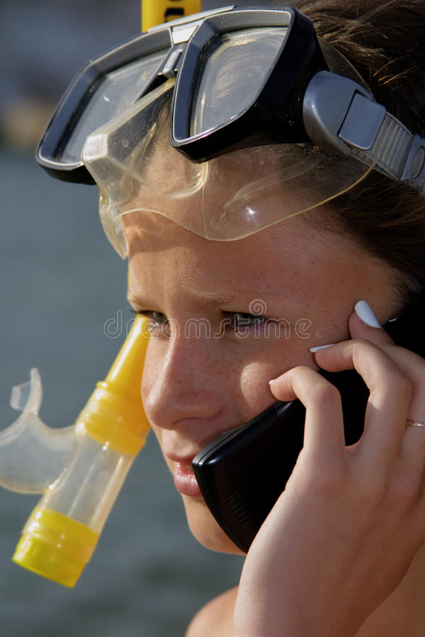 Girl at the sea. Girl in a diving mask talks by telephone stock image
