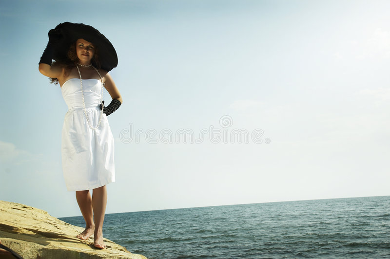 Girl by the sea. The beautiful young girl in a black hat and white dress on a coast of the sea stock image