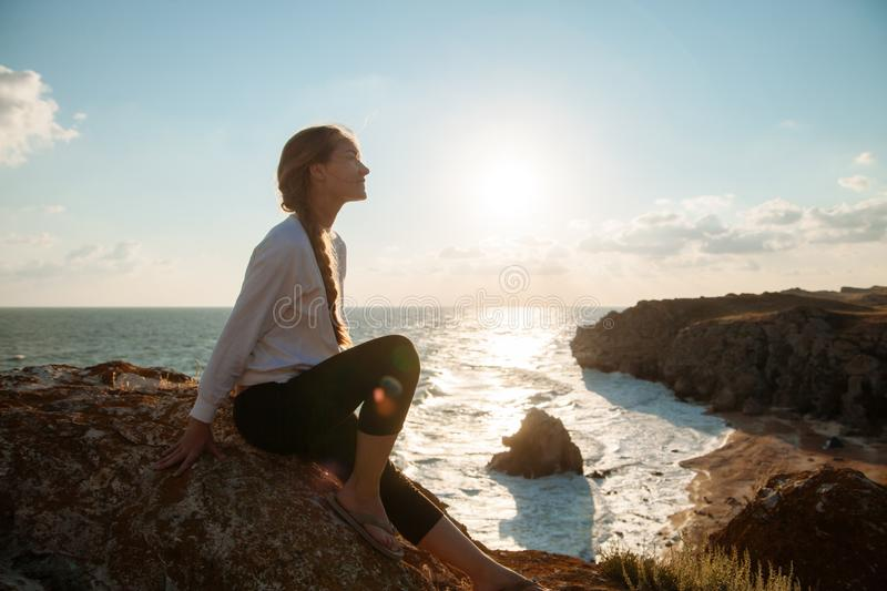 Girl on the sea coast. A young girl sitting on a rock on the background of the sea coast royalty free stock image
