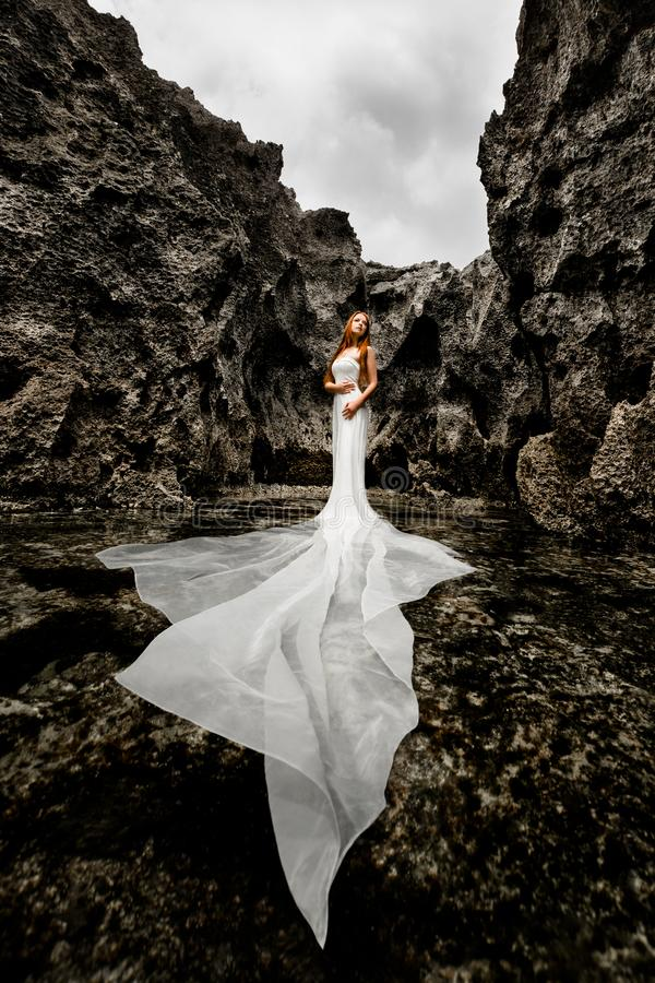 Girl in a sea creek surrounded by cliffs stock images