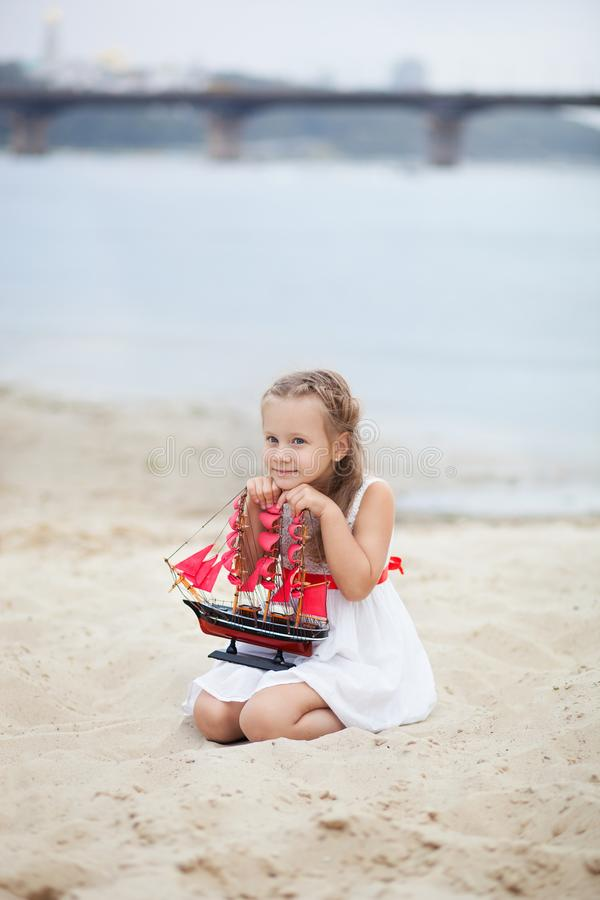 Girl on the sea with a ship. little girl wait boat with scarlet sail. The girl in the white board on the beach with scarlet sails royalty free stock images