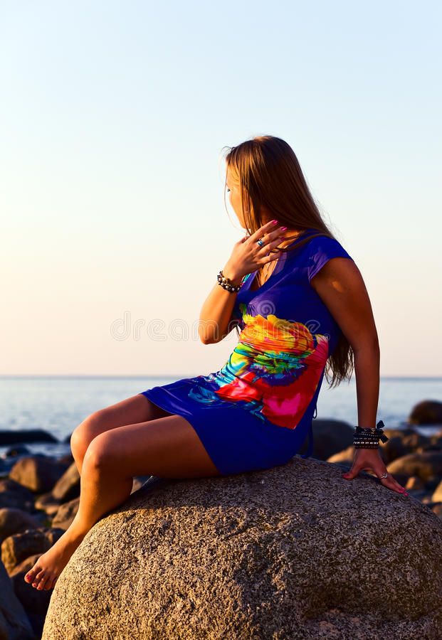 Girl on seacoast before a sunset