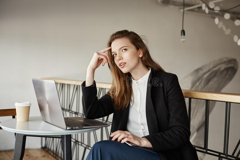 Girl searches inspiration in coffee shop. Indoor portrait of gorgeous slender woman in stylish outfit sitting in cafe stock images