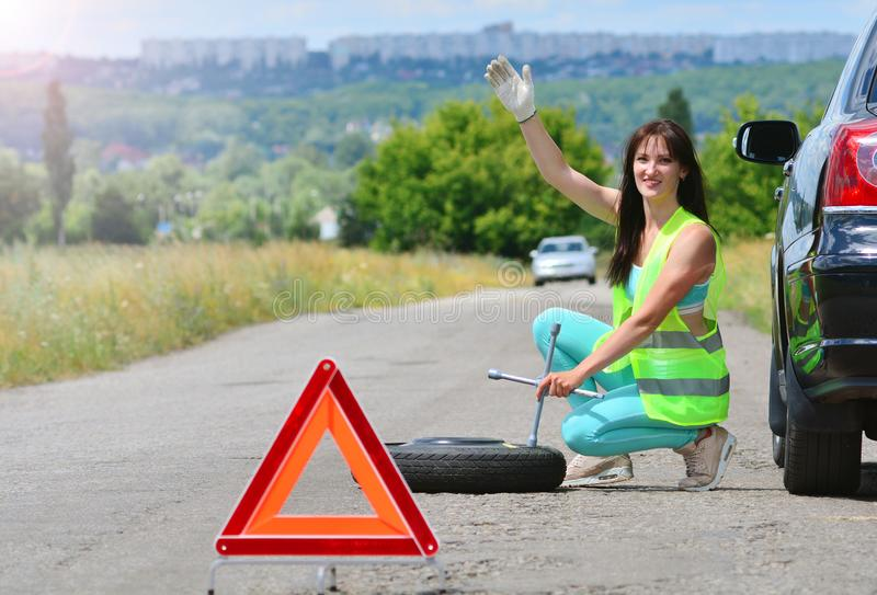 Girl searching for help with spare wheel replacement. royalty free stock photo