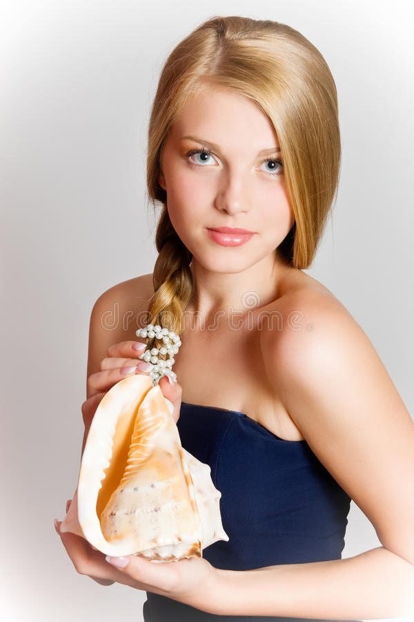 Girl with seashell. Glamour portrait of beautiful blond woman model with fresh daily makeup and healthy hair. Girl with seashell stock photography