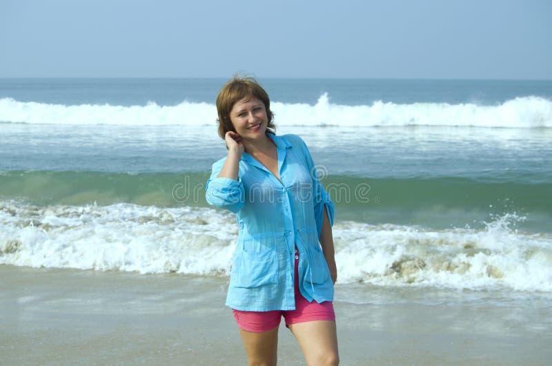 Girl on the seashore smiles stock image