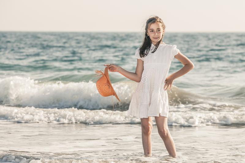 Girl on the seashore wearing an orange hat and a white dress stock images