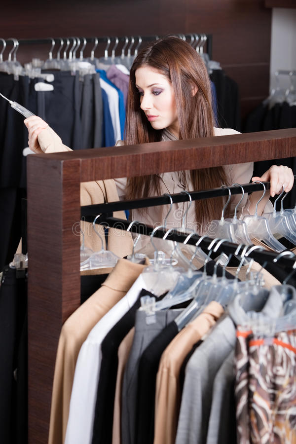 Girl is seeking for perfect garments. Woman is seeking for perfect garments stock image