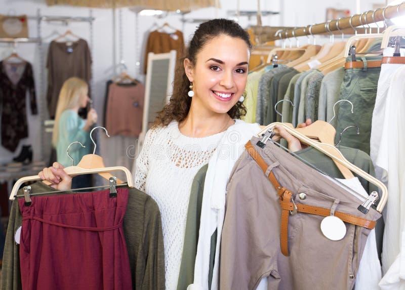 Girl selecting new garments at the store. Smiling young brunette selecting new garments at the store royalty free stock photos