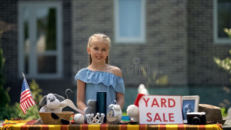 Girl selling old toys on yard sale, earning pocket money, young business lady. Stock photo royalty free stock images