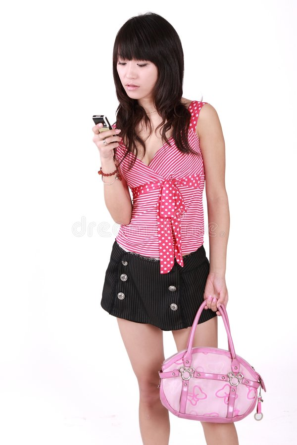 Girl sending an sms. A beautiful Asian girl is sending an sms stock photo