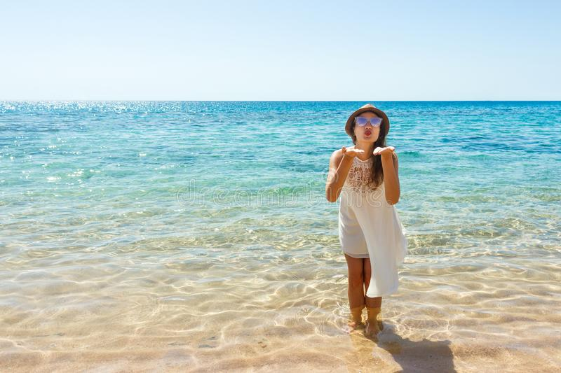 Girl sends an air kiss to the camera. a beautiful carefree Woman relaxing at the beach enjoying her sun white dress. girl sends an stock image