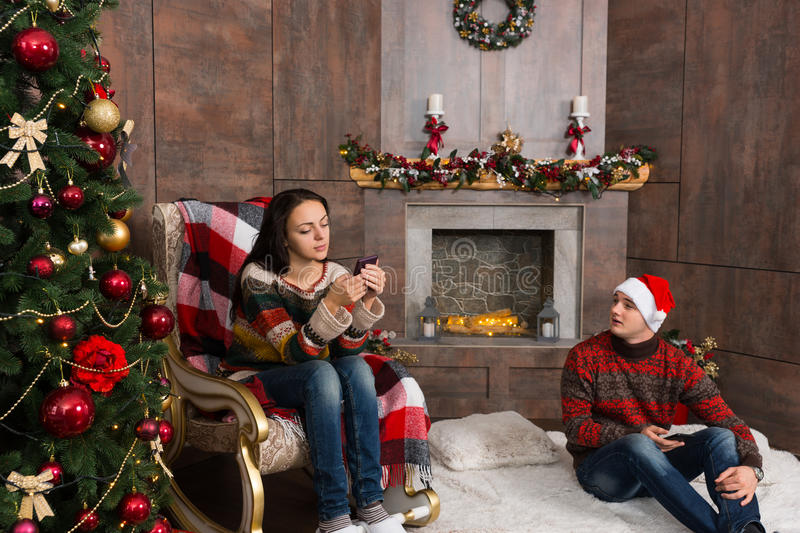 Girl serfing the Internet on her mobile phone while her boyfriend sitting on a rug in the room with decorated fireplace and Chris. Girl sitting on the rocking royalty free stock image